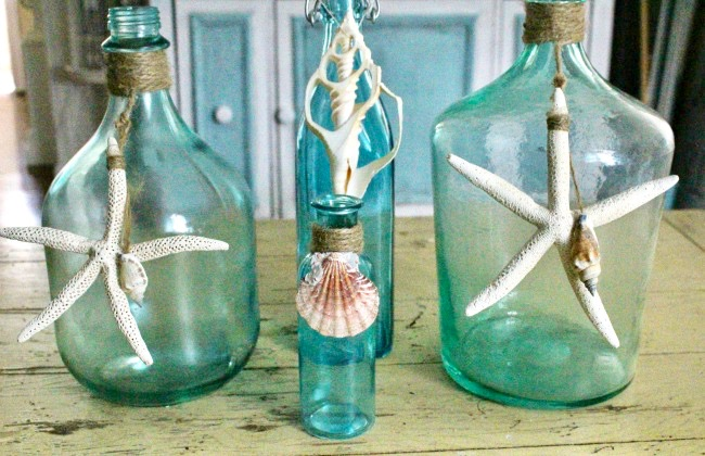 set of four bottles with star fish and sea shells painted blue on coffee table
