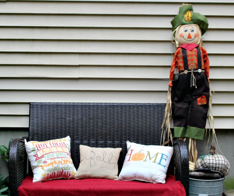 Bench with fall pillows and scarecrow