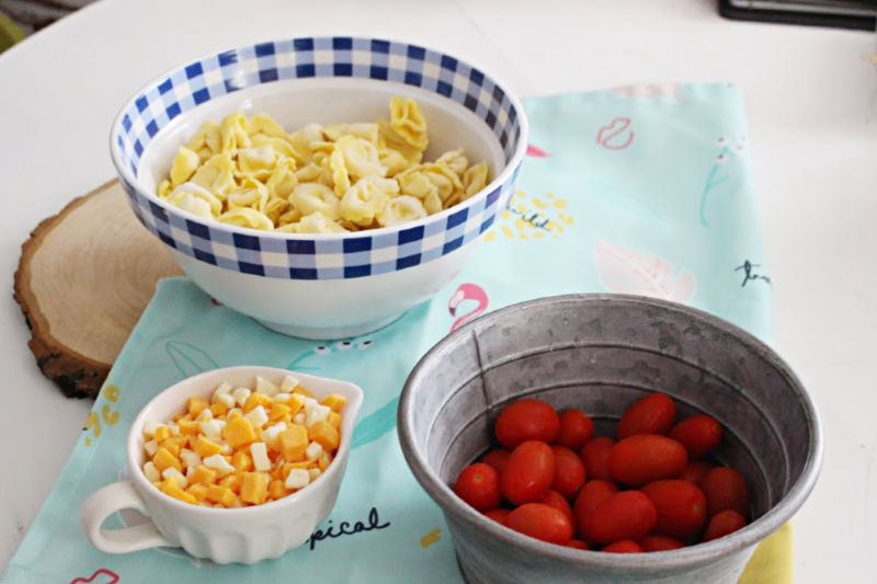 ingredients for pasta salad in separate bowls on table