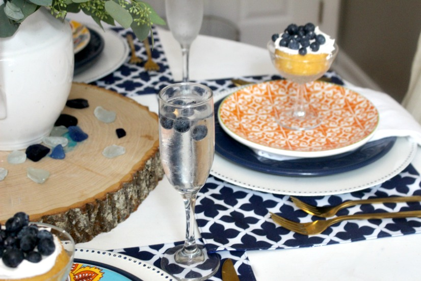 summer tablescape with orange dishes and blueberries in champagne