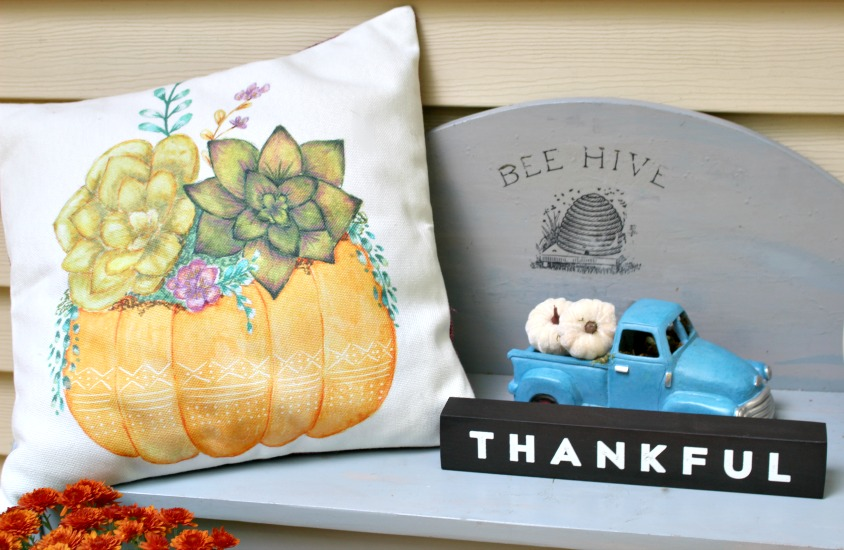 gray bench with pumpkin pillow and thankful sign