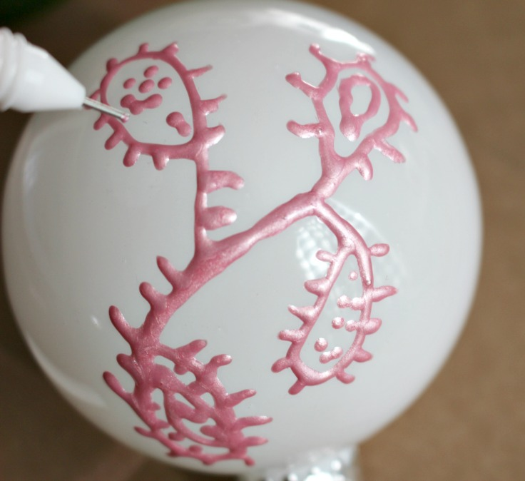 hand painting on white ornaments with pink paint