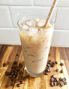 iced coffee on counter with coffee beans