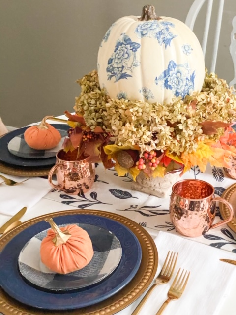 blue and orange fall tablescape with copper mugs