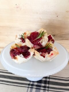 cranberry brie bites on white cake plate