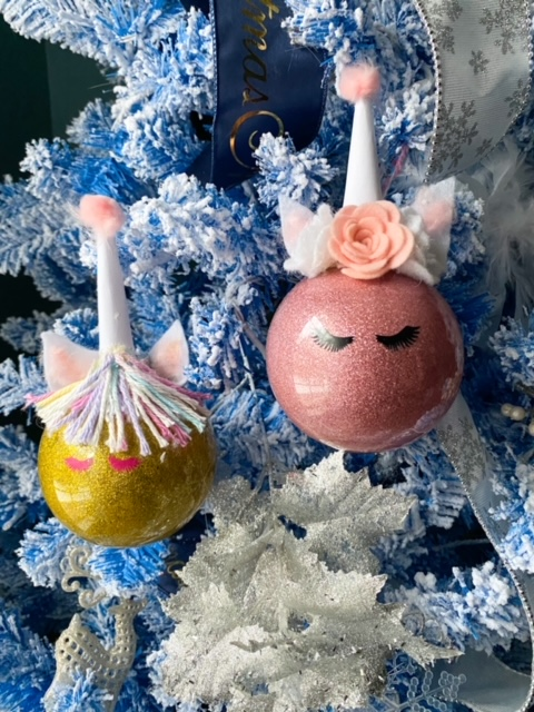 two unicorn ornaments hanging on tree