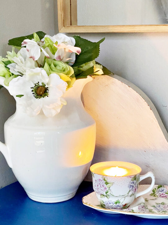 diy teacup candle on blue table with vase of flowers