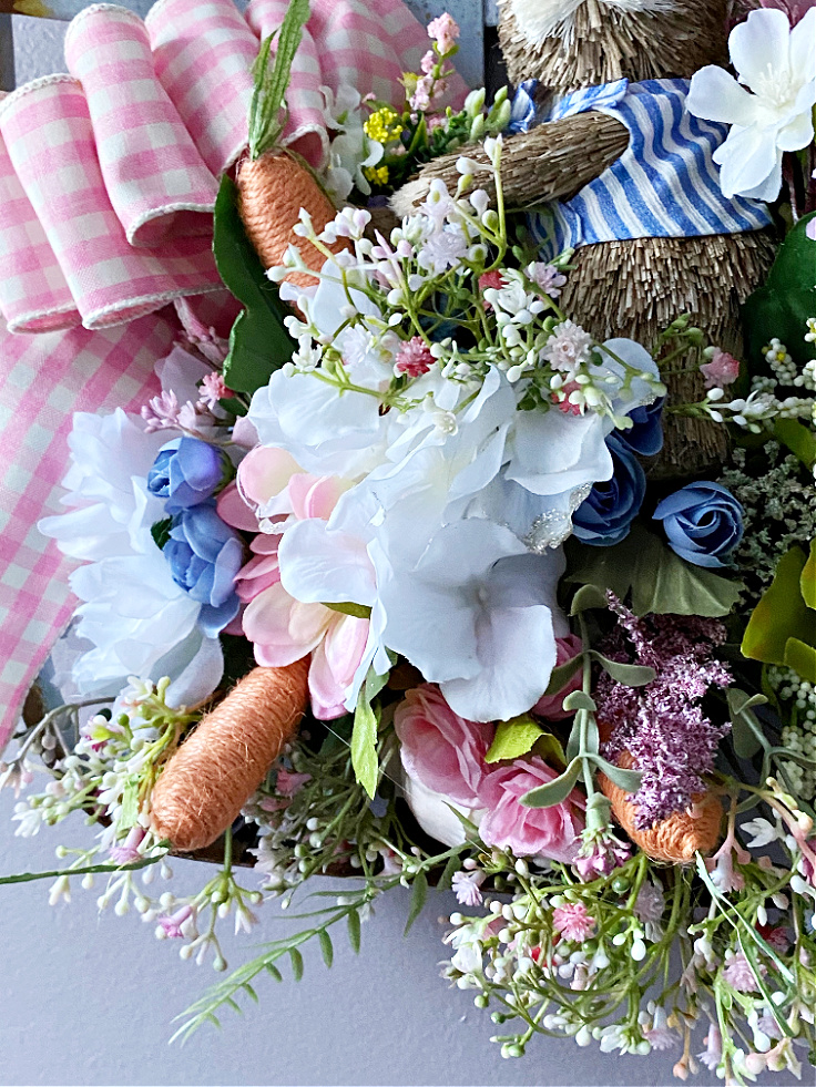 close up of spring flowers in tobacco basket wreath