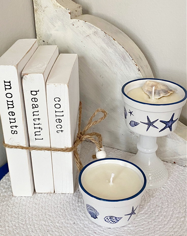 soy candles in coastal dishes on table with books