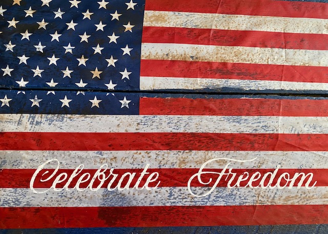 celebrate freedom painted on wood sign