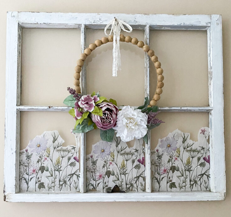 old window hanging on wall with wood bead wreath