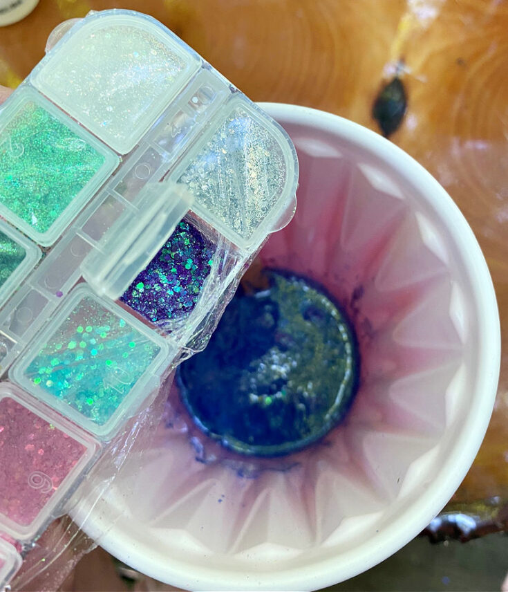 pouring glitter into mixed resin