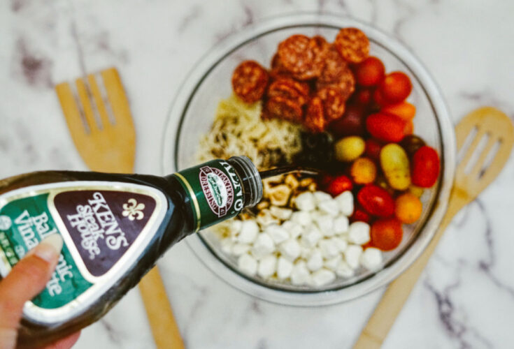 pouring Balsamic dressing on Pasta Salad